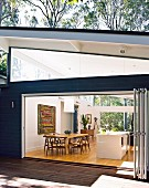 View through open folding doors of dining table and kitchen island in open-plan kitchen
