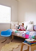 Toddler on bed with colourful patchwork blanket next to blue, designer rocking chair