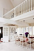 White, country-house-style open-plan dining area with gallery and white-painted wooden furniture