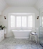 White, wood-panelled bathroom with Carrara marble floor and free-standing, white bathtub