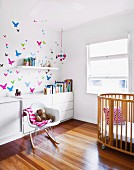 Classic rocking chair next to cot and white sideboard against wall with butterfly motifs in sunny nursery