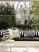 Black and white cushions on masonry bench with glass panel as transparent backrest
