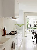White designer kitchen with integrated sink in Corian worksurface; dining area with Thonet chairs