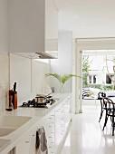 weiße Designerküche mit integrierten Spülbecken in Corian Arbeitsplatte; Essplatz mit Thonetstühlen