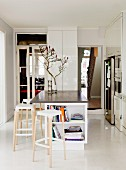 Bar stools at island counter in minimalist, white designer kitchen