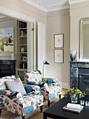Armchairs with cheerful, floral upholstery in classic interior with stucco ceiling and open fireplace