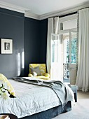 Classic bedroom with pale yellow textile accents combined with dark grey walls