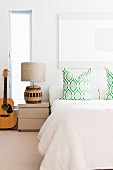 Scatter cushions on double bed, vertical window slit behind ethnic bedside lamp and guitar