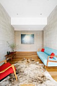 Animal-skin rug on wooden floor between armchair with red cover and blue, 50s-style sofa in anteroom with pale grey stone walls