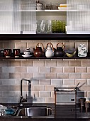 Detail of retro kitchen counter below tiled wall and wall units