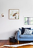 Window and picture on white wall above sofa with scatter cushions