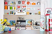 Colourful crockery on white kitchen shelving; brightly coloured thermos flasks on worksurface in foreground