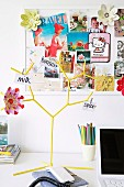 Postcards and flower decorations on pinboard behind yellow, tree-shaped rack with notes pegged to branches