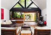 View from interior with seating area through triangular, glazed gable to terrace with pergola and tropical garden