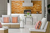 Mainly white designer furniture in living-dining room with splashes of colour provided by tiled kitchen wall and bright, striped cushions