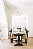 Dark dining table and chairs in bright room with chandelier and open doorway leading to white kitchen
