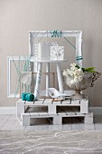 Stacked, white wooden pallets with white picture frames and large cup with white tulips