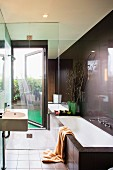 Designer bathroom in dark brown - wash basin and bathtub in front of a glass shower stall with access to the terriace