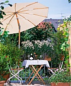 Blooming balcony with shady seating below parasol