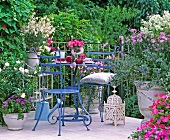 Flowering plants in deep pink, rose and white on balcony with delicate furniture