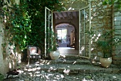 Open terrace door of stone-built, Mediterranean country house with view into interior