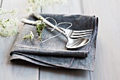 Cutlery and heart made from wire and herbs on napkin