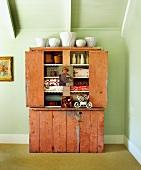 Ramponierter Vintage-Schrank mit Vasen, Stoffen und altmodischer Deko in Landhauszimmer unterm Dach