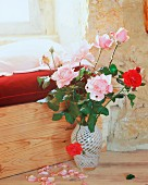 Roses in vase in front of window niche in Château Maignaut (Pyrenees, France)