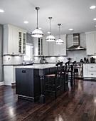 Geräumige, weisse Küche mit zentraler Kücheninsel in Schwarz