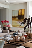 Modern living room furniture combined with hot pink flowers and horse figurine on coffee table