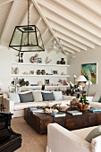 Bright, attic living room with solid wood, antique coffee table and objet d'art on shelving