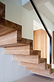 Luxurious, solid wood staircase with metal bannister in modern interior