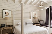 White canopied bed with antique bedside tables and upholstered window seat with practical drawers