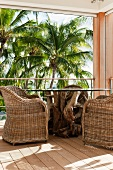 Corner of balcony with rustic table, comfortable wicker armchairs and view of palm trees