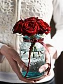 Hände halten Einmachglas mit kleinem Rosenstrauss