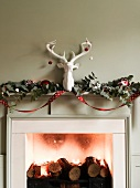 Fireplace with logs, tealights, Christmas decorations and ornamental stag's head