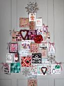 Weihnachtskarten in Tannenbaumform arrangiert an der Wand