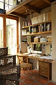 Home office with rustic desk top made from thick pine board with live edge, shelving made from scrap wood and old, artistic spiral staircase in house with many reclaimed elements