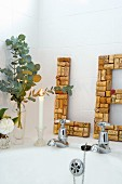 Lit candle, vases of flowers and large letters hand-crafted from corks leaning on white tiled wall on edge of bathtub