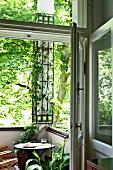 Blick durch offene Tür auf Bistrotisch in Balkonecke mit berankter Stütze