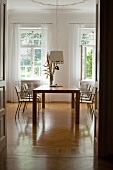 View of modern dining table and chairs in classic setting through doorway