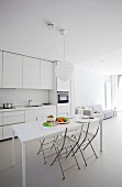 White, designer interior with dining table and folding chairs in front of open-plan kitchen