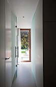 Schmaler Gang und Blick durch offene Glastür auf Gartentür in zeitgenössischer Wohnung