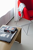 Red designer chair next to books on dimple side table