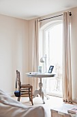 Antique, white-painted table and vintage rush-bottom chair in front of French doors in corner of bright room