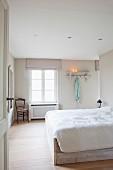 Freundliches Schlafzimmer mit hellem Dielenboden und einfachem Bettkasten aus hellem Holz