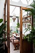 Blick durch geöffnete Holztür mit Glaseinsatz in den Speiseraum in afrikanischem Stil