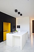 Clarity and elegance in minimalist fitted kitchen with white island counter and black and yellow fronts