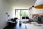 Heller, moderner Wohnraum mit schwarzer Ledercouch, verchromter Stehlampe und einem langen Wandregal; im Hintergrund die sonnige Gartenterrasse