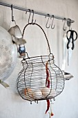 Eggs in old wire basket and other kitchen utensils hanging from butchers' hooks